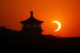 BEIJING - JANUARY 15:  The moon begins to obstruct the view of the sun from earth during a soloar eclipse at the Tian'anmen Square on January 15, 2010 in Shenyang, Liaoning Province of China. The eclipse, which first became visible in Tamil Nadu city of Kanyakumari, is predicted to be the longest of its kind for the next 1000 years.  (Photo by Feng Li/Getty Images)