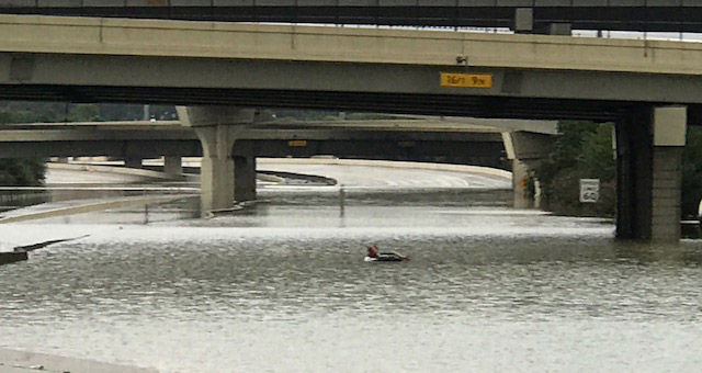 """Flooding on Interstate 10 closed the major roadway to downtown Houston. Note, you can see someone on the flooded highway floating in a tube like taking a ride along a """"lazy river"""" at a theme park. (WTOP/Steve Dresner)"""