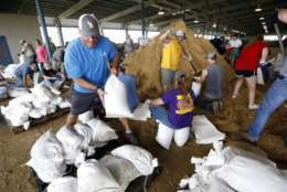 A volunteer loads sand bags on a pallet as others fill them for resident distribution, Tuesday, Aug. 29, 2017, at the Burton Coliseum in Lake Charles, La. Each pallet was loaded with 20 sand bags. (AP Photo/Rogelio V. Solis)