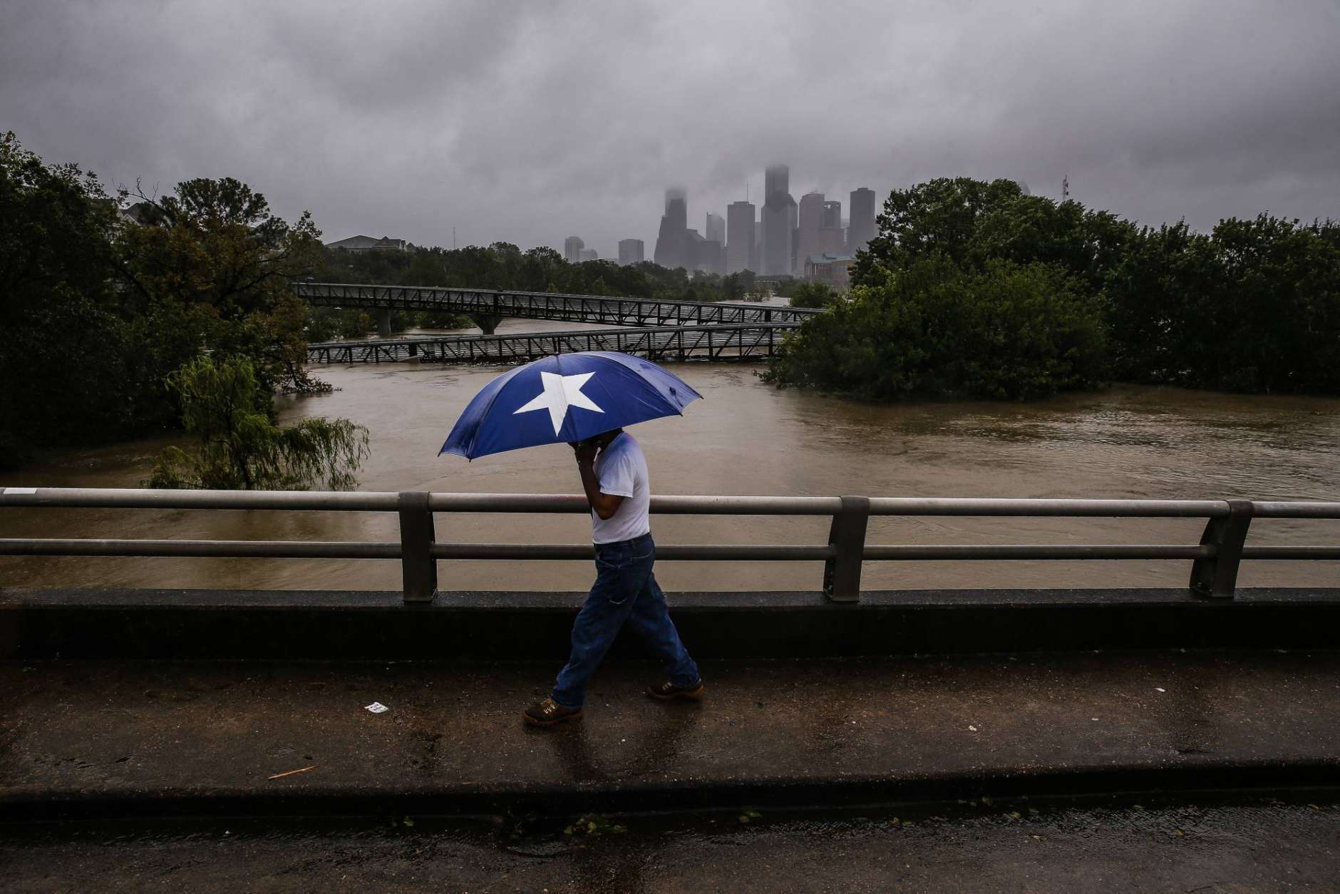 Armando Bustsamante walks along the street over Buffalo Bayou as flood waters from Tropical Storm Harvey flow toward downtown Houston Tuesday, Aug. 29, 2017.  More than 17,000 people are seeking refuge in Texas shelters, the American Red Cross said. With rescues continuing, that number seemed certain to grow. (Michael Ciaglo/Houston Chronicle via AP)