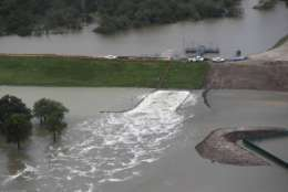 In this aerial photo,  water is released from the Addicks Reservoir as floodwaters rise from Tropical Storm Harvey on Tuesday, Aug. 29, 2017, in Houston.   (Brett Coomer/Houston Chronicle via AP)
