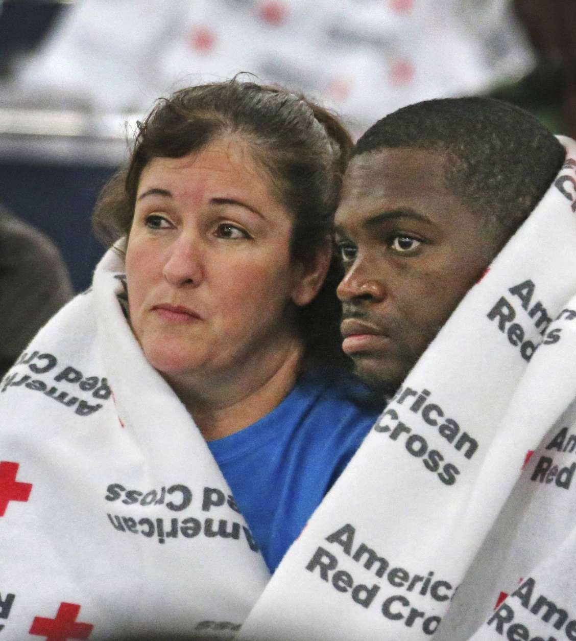 Displaced South Houston residents Oralia Guerra and Diamond Robinson huddle together to stay warm underneath Red Cross blankets at the George Brown Convention Center in Houston on Monday, Aug. 28, 2017, in the wake of Tropical Storm Harvey. Floodwaters reached the rooflines of single-story homes Monday and people could be heard pleading for help from inside as Harvey poured rain on the Houston area for a fourth consecutive day after a chaotic weekend of rising water and rescues. (Louis DeLuca/The Dallas Morning News via AP)