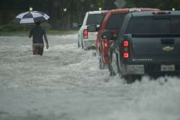 A pedestrian crosses a street inundated by floodwaters from Tropical Storm Harvey on Sunday, Aug. 27, 2017, in Houston, Texas. (AP Photo/Charlie Riedel)