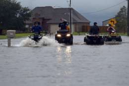 Kids ride an ATV in a street flooded by Tropical Storm Harvey, in the Clearfield Farm subdivision in Lake Charles, La., Tuesday, Aug. 29, 2017. (AP Photo/Gerald Herbert)