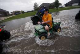 Kids pull a toy with an ATV in a street flooded by Tropical Storm Harvey, in the Clearfield Farm subdivision in Lake Charles, La., Tuesday, Aug. 29, 2017. (AP Photo/Gerald Herbert)