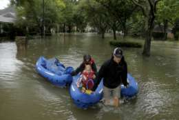People evacuate a neighborhood inundated by floodwaters from Tropical Storm Harvey on Monday, Aug. 28, 2017, in Houston, Texas. (AP Photo/Charlie Riedel)