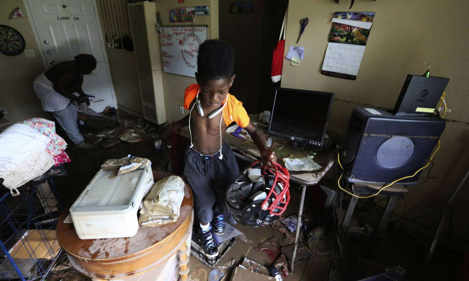 Darrington Mason, 11, right, pulls his football helmet from his flooded home where he lives with his grandmother Gillis Leho in Houston, Texas, Wednesday, Aug. 30, 2017. Leho and the her grandchildren had been planning to evacuate by car but had to quickly escape through a window of their home as floodwaters brought on by Tropical Storm Harvey rushed in from nearby Buffalo Bayou. (AP Photo/LM Otero)