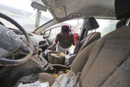 Gillis Leho looks for documents in her car that was covered by floodwaters brought on by Tropical Storm Harvey in Houston, Texas, Wednesday, Aug. 30, 2017. Leho had been planning to evacuate in her car but had to quickly escape through a of her home with her grandchildren as rising waters rushed in from nearby Buffalo Bayou. (AP Photo/LM Otero)