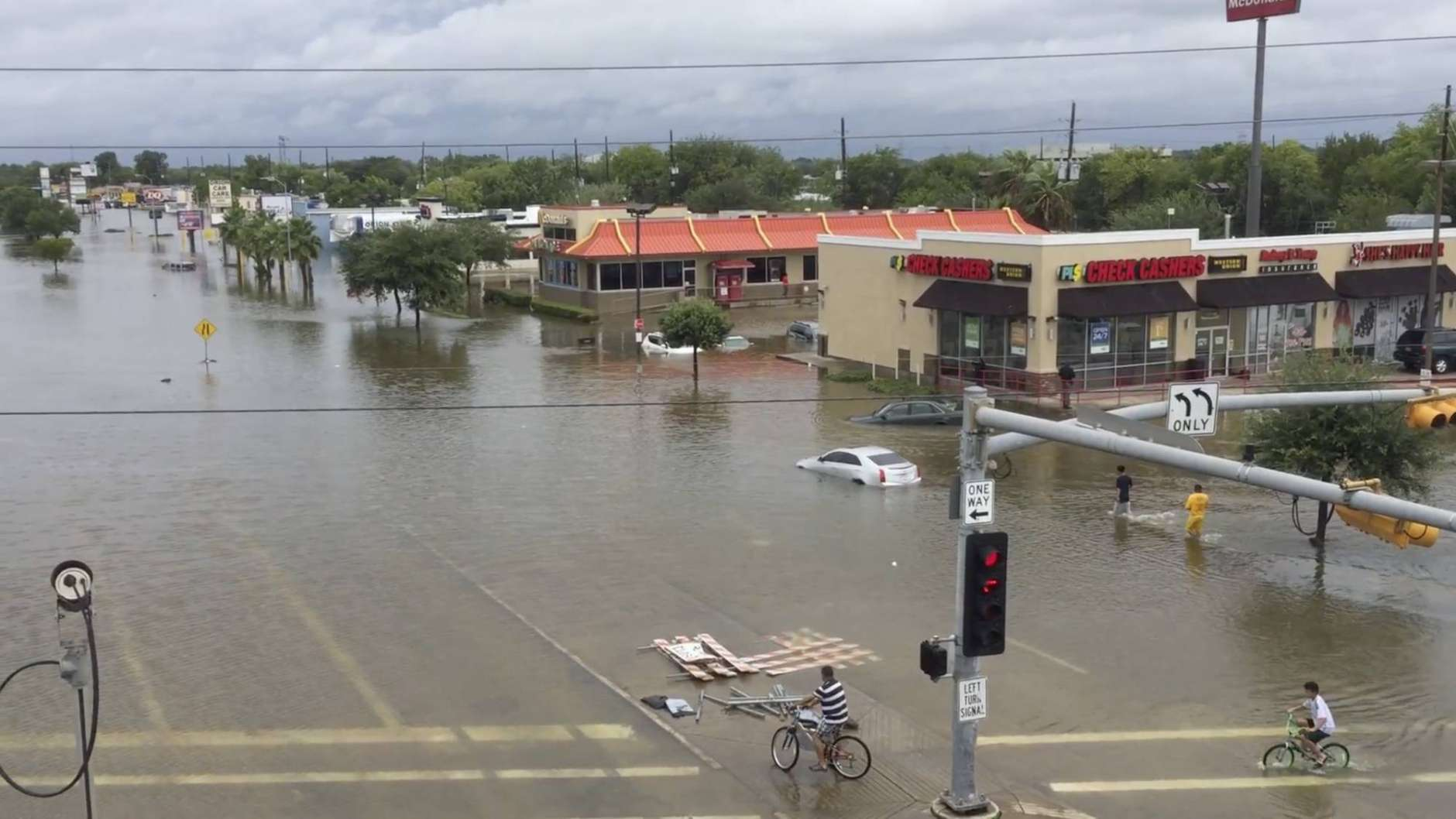 This image made from a video shows a view from U.S. Route 59 of flooding on West Bellfort Avenue in Houston, Sunday, Aug. 27, 2017. The remnants of Hurricane Harvey sent devastating floods pouring into Houston Sunday as rising water chased thousands of people to rooftops or higher ground. (DroneBase via AP)