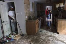 Craig Hardy helps clean out the home of Michael Boyd, which was flooded with in the aftermath of Tropical Storm Harvey on Wednesday, Aug. 30, 2017, in Houston. Harvey's floodwaters started dropping across much of the Houston area, but many thousands of homes in and around the nation's fourth-largest city were still swamped and could stay that way for days or longer.  (Brett Coomer/Houston Chronicle via AP)