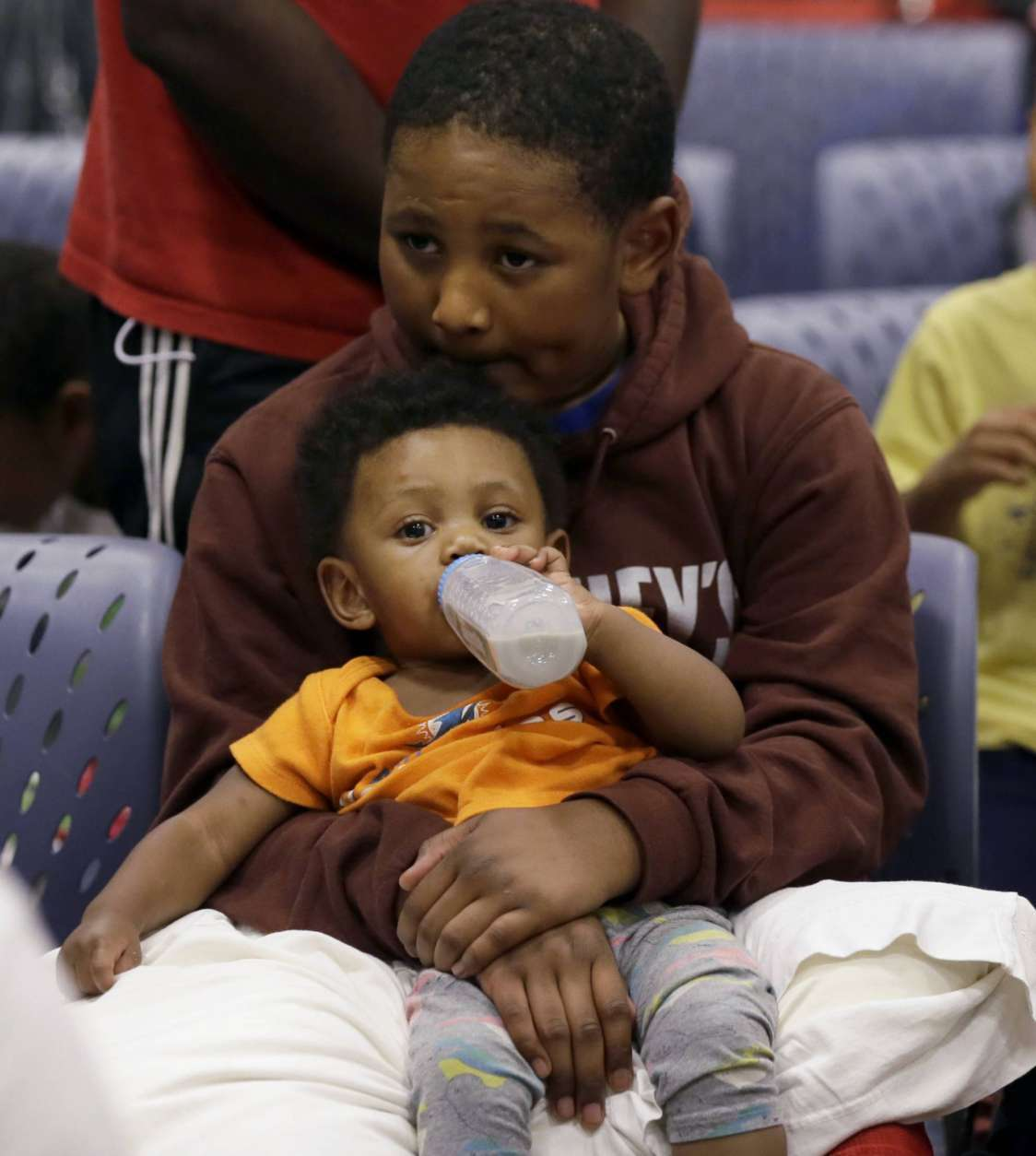 Evacuee Edward Jones, 11, holds his step-brother Mickel Duane Batts at the Lakewood Church in Houston, Tuesday, Aug. 29, 2017. Joel Olsten and his congregation have set up their church as a shelter for evacuees from the flooding by Tropical Storm Harvey. (AP Photo/LM Otero)