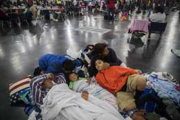 Oscar Galindo, Donato Galindo, 2, Oscar Galindo, 11, Andre Galindo, 9, and Maria Rodriguez relax while taking shelter at the George R Brown Convention Center on Monday, Aug. 28, 2017, in Houston, after living inside a car since Saturday after the rain from the Tropical Storm Harvey flooded their home in Dickinson, Texas. (Marie D. De Jesus/Houston Chronicle via AP)