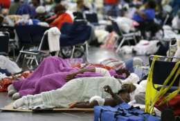 People sleep on the floor at the George R. Brown Convention Center that has been set up as a shelter for evacuees escaping the floodwaters from Tropical Storm Harvey in Houston, Texas, Tuesday, Aug. 29, 2017. (AP Photo/LM Otero)