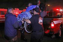 Lake Charles rescue personnel help lower this wheelchair bound resident from the back of a vehicle late Monday night, Aug. 28, 2017, in Lake Charles, La., after flooding from Harvey's almost constant rain over the last two days overcame the city's drainage system, flooding several subdivisions and necessitating home rescues. (AP Photo/Rogelio V. Solis)