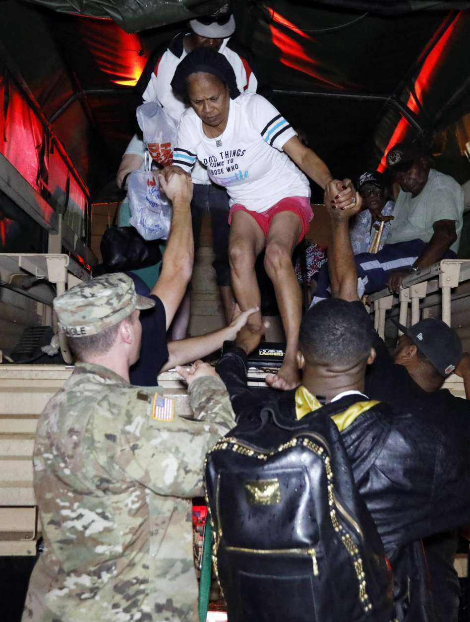 Lake Charles rescue personnel help residents exit from the back of a vehicle late Monday night, Aug. 28, 2017, in Lake Charles, La., after flooding from Harvey's almost constant rain over the last two days overcame the city's drainage system, flooding several subdivisions and necessitating home rescues. (AP Photo/Rogelio V. Solis)