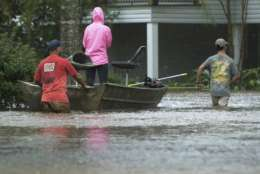 Residents of Cypress Lake Dr. use boats to transport others and retrieve items from flooded homes in Moss Bluff, La., Tuesday, Aug. 29, 2017. (Rick Hickman/American Press via AP)