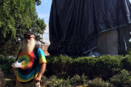 John Miska, a veteran and self-proclaimed free-speech advocate wearing a tie-die T-shirt and carrying a legal weapon, cut away a small section of the black tarp before Charlottesville police ordered him stop Wednesday. (WTOP/Shawn Anderson)