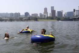 People cool off in the Willamette River with the downtown skyline visible in the background in Portland, Ore., Wednesday, Aug. 2, 2017. Scorching temperatures are predicted for the Northwest Wednesday and Thursday, with forecasters saying Seattle and Portland could top triple digits and break records. (AP Photo/Don Ryan)