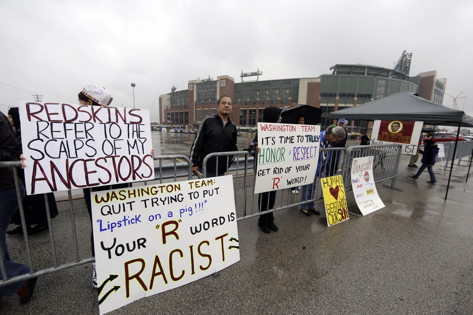 The ban on Redskins gear at Green Acres School came after a classroom discussions about team logos that are based on race or ethnicity. In this photo, people protest the Redskins name outside Lambeau Field before an NFL football game between the Green Bay Packers and the Washington Redskins Sunday, Sept. 15, 2013, in Green Bay, Wis. (AP Photo/Tom Lynn)
