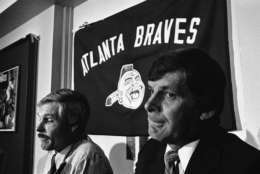 In 2013, the Braves considered bringing back their logo they retired after 1989, seen in the background here in this 1981 photo, on spring training hats however outrage prompted them to change the logo.  FILE. Bobby Cox (right) listens as Atlanta Brave Owner Ted Turner (left) announces at a news conference on Thursday, Oct. 8, 1981 in Atlanta that Cox would not be manager of the ball club next season. Cox has been with th Braves since 1978.   No replacement was named. (AP Photo/ Joe Holloway)