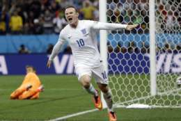 FILE - This is a Thursday, June 19, 2014 file photo of Uruguay's goalkeeper Fernando Muslera looks back as England's Wayne Rooney celebrates after scoring his side's first goal during the group D World Cup soccer match between Uruguay and England at the Itaquerao Stadium in Sao Paulo, Brazil.  England striker Wayne Rooney announced his immediate retirement from international football on Wednesday Aug. 23, 2017. (AP Photo/Kirsty Wigglesworth, File)