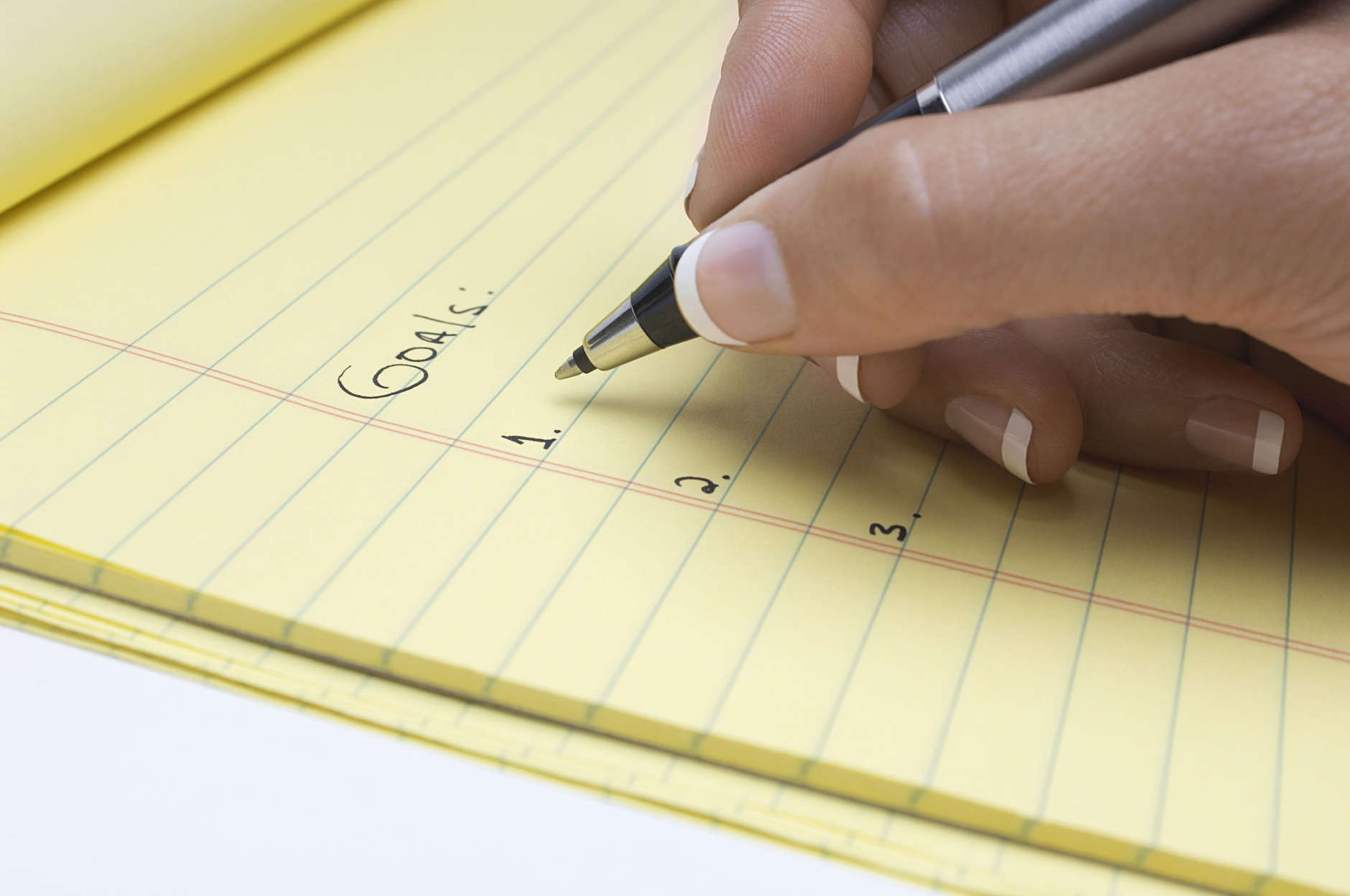Woman writing list of goals,  close-up of hand