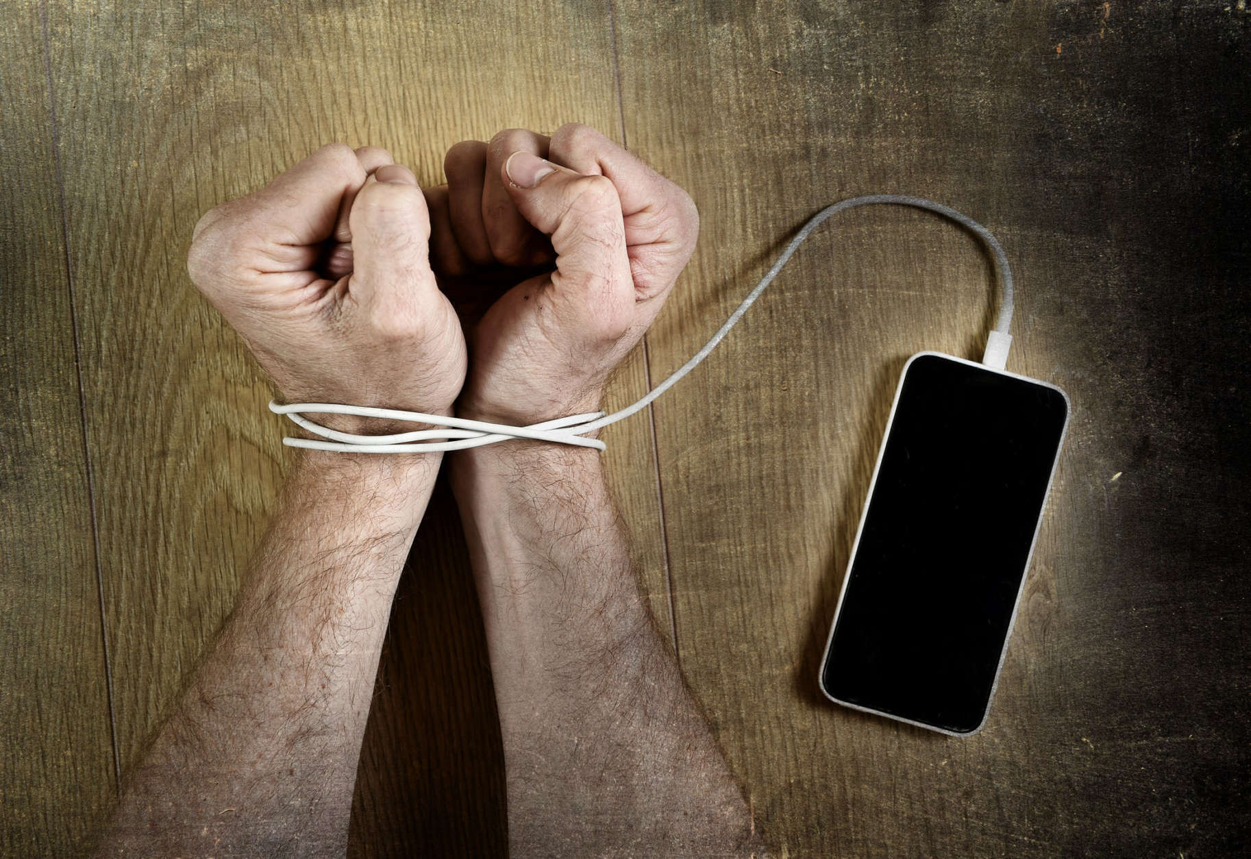 man hands trapped and wrapped on wrists with mobile phone cable as handcuffs in smart phone networking and communication technology addiction concept