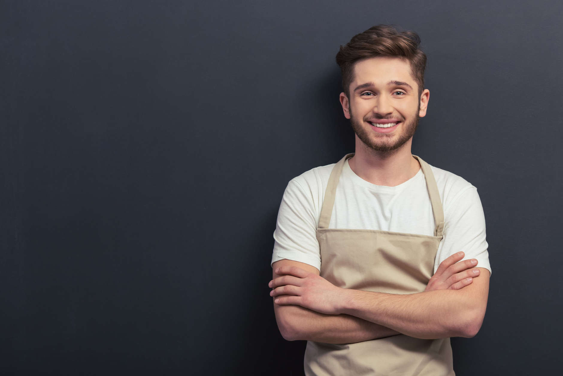 Handsome young man in apron is looking at camera and smiling, standing with crossed arms against blackboard