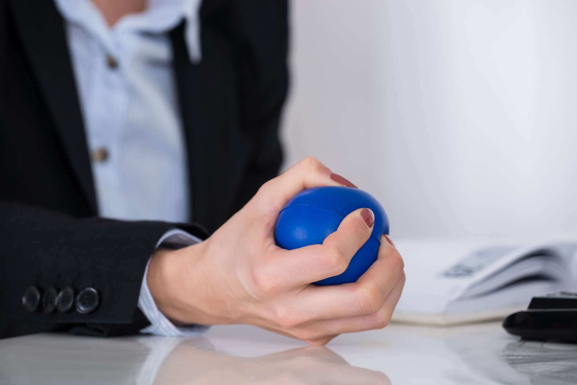 Close-up Of Businessperson Hand Squeezing Blue Stressball In Hand At Desk