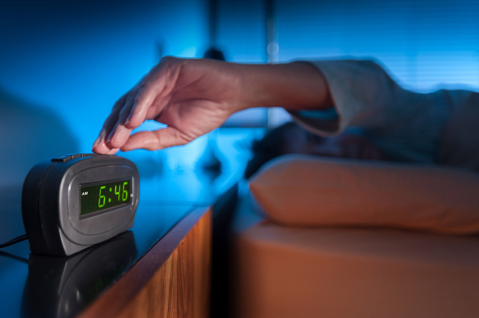 Woman pressing snooze button on early morning digital alarm clock (Thinkstock)