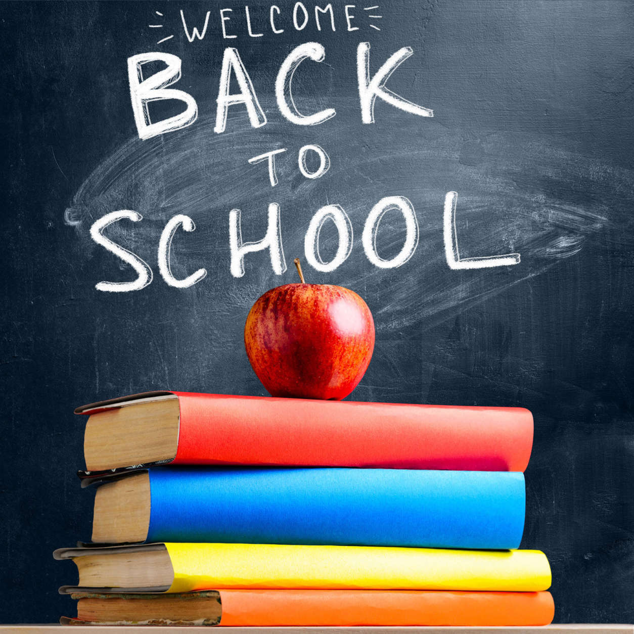Back to School. Books and fresh apple against chalkboard (Thinkstock)