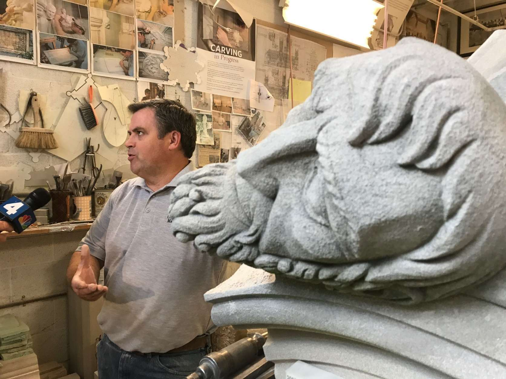 National Cathedral stone carver Sean Callahan stands in the stone masons' workshop on the National Cathedral grounds where a majority of the restoration work is done. (WTOP/Megan Cloherty)