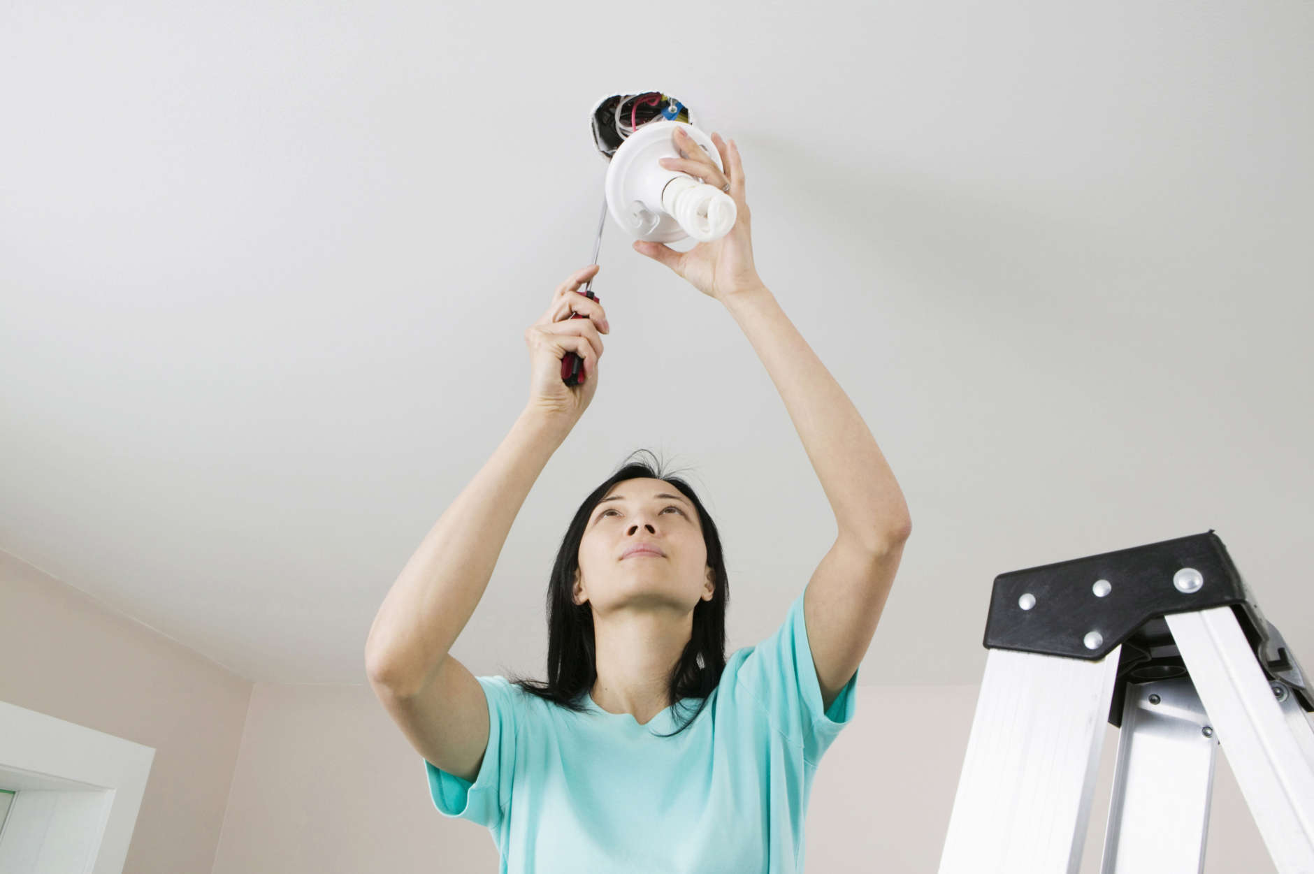 Low angle view of a young woman fixing a light fixture