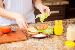 Closeup of the hands of young woman preparing a sandwich at home (Thinkstock)