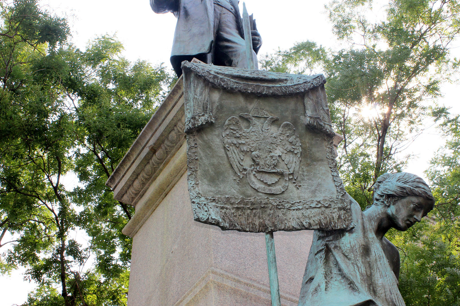 The figure holds the Scottish Rite banner. Pike is also depicted holding a book of Freemason philosphy that he wrote. The Scottish Rite paid for the statue to recognize Pike's dedication to their organization and ideals of moral and social improvement. Earlier in his life, he also supported slavery and joined the Confederate Army. The monument, erected in 1901, was the scene of a protest earlier this week and D.C. officials are now calling for its removal.  (WTOP/Amanda Iacone)