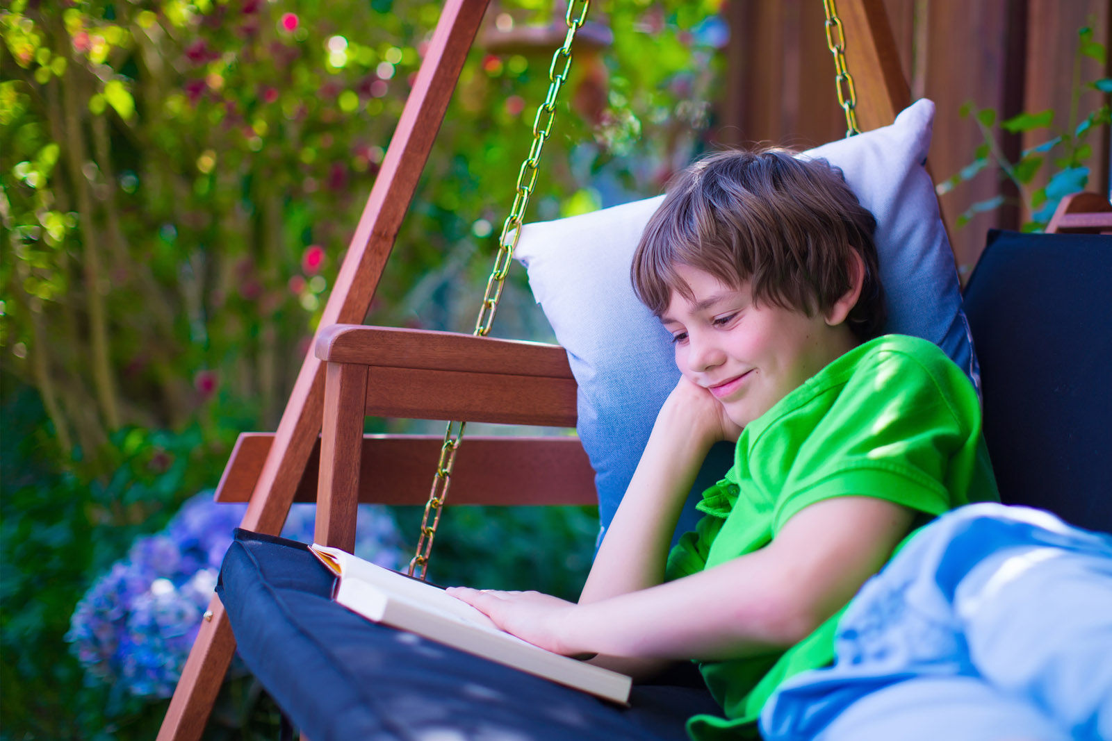 Happy school boy reading a book in the backyard. Child relaxing in a garden swing with books. Kids read during summer vacation. Children studying. Teenager kid doing homework outdoors. (Thinkstock)