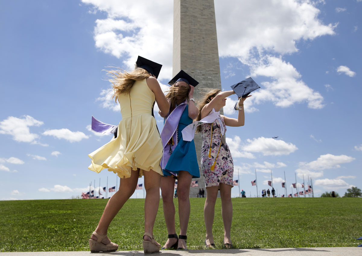 George Washington University graduates Serena Williams, left, and Hannah Raymond, center and Katie Kenny, right, struggle against a strong wind as they pose for graduations pictures near the Washington Monument, Sunday, May 15, 2016, in Washington, after their commencement ceremony on the National Mall. (AP Photo/Carolyn Kaster)
