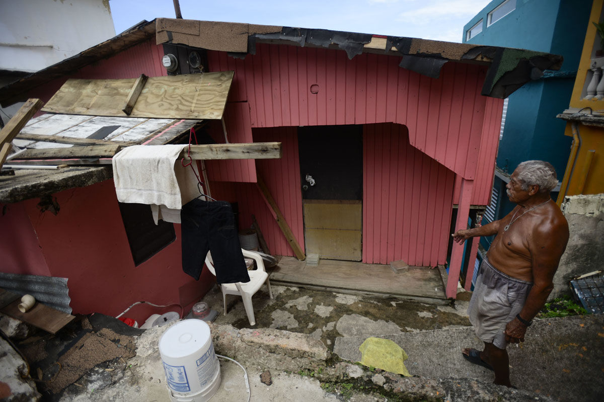La Perla resident Ramon Marrero, 76, looks at his battered residence after the scourge of Hurricane Maria, in San Juan, Puerto Rico, Monday, Sept. 25, 2017. The island territory of more than 3 million U.S. citizens is reeling in the devastating wake of Hurricane Maria. (AP Photo/Carlos Giusti)