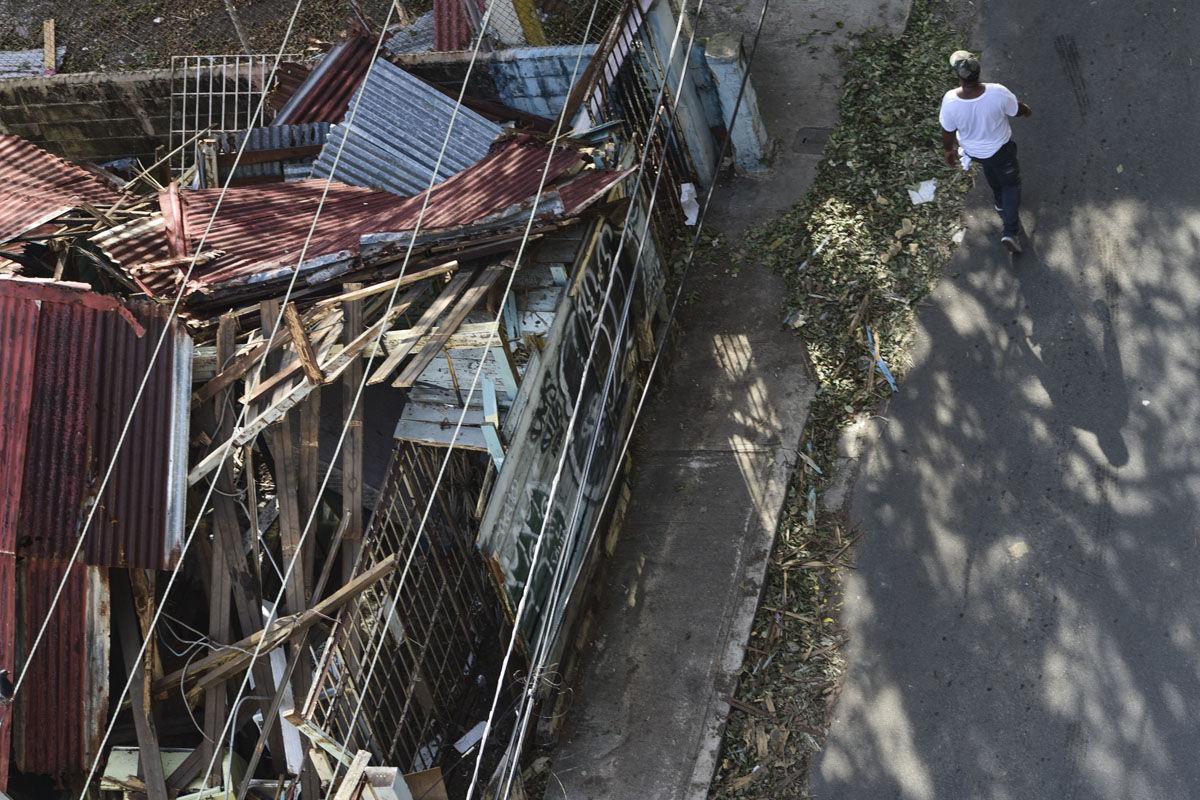 A person walks by a damaged building in of El Gandul Community in Santurce after Hurricane Maria, in San Juan, Puerto Rico, Monday, Sept. 25, 2017. (AP Photo/Carlos Giusti)