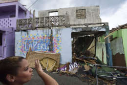 Yashira Gomez, president of La Perla community board shows part of the devastation left by Hurricane Maria, in San Juan, Puerto Rico, Monday, Sept. 25, 2017. The island territory of more than 3 million U.S. citizens is reeling in the devastating wake of Hurricane Maria. (AP Photo/Carlos Giusti)