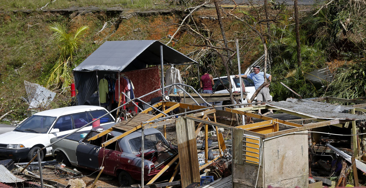Jose Garcia Vicente, right, works with Jose Colon, as he starts to salvage his destroyed home, in the aftermath of Hurricane Maria, in Aibonito, Puerto Rico, Monday, Sept. 25, 2017. The U.S. ramped up its response Monday to the humanitarian crisis in Puerto Rico while the Trump administration sought to blunt criticism that its response to Hurricane Maria has fallen short of it efforts in Texas and Florida after the recent hurricanes there. (AP Photo/Gerald Herbert)