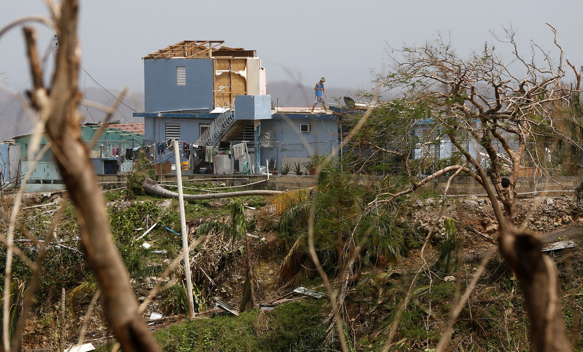 A man sweeps his heavily damaged home in Montebello, Puerto Rico, in the aftermath of Hurricane Maria, Tuesday, Sept. 26, 2017. Five days after the Category 4 storm slammed into Puerto Rico, many of the more than 3.4 million U.S. citizens in the territory were still without adequate food, water and fuel. Flights off the island were infrequent, communications were spotty and roads were clogged with debris. Officials said electrical power may not be fully restored for more than a month. (AP Photo/Gerald Herbert)