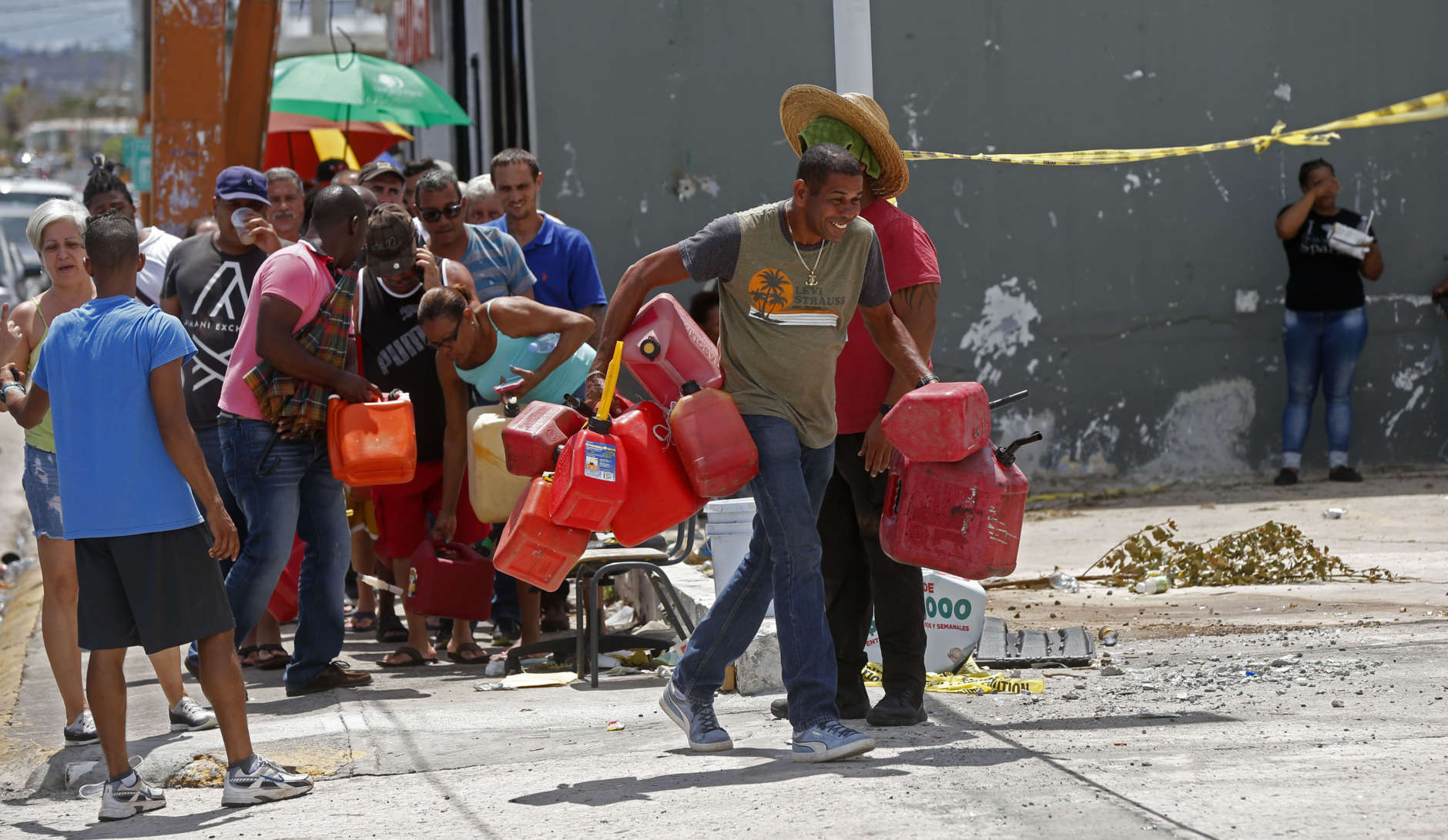 A man runs as people line up with gas cans to get fuel from a gas station, in the aftermath of Hurricane Maria, in San Juan, Puerto Rico, Monday, Sept. 25, 2017. The U.S. ramped up its response Monday to the humanitarian crisis in Puerto Rico while the Trump administration sought to blunt criticism that its response to Hurricane Maria has fallen short of it efforts in Texas and Florida after the recent hurricanes there. (AP Photo/Gerald Herbert)
