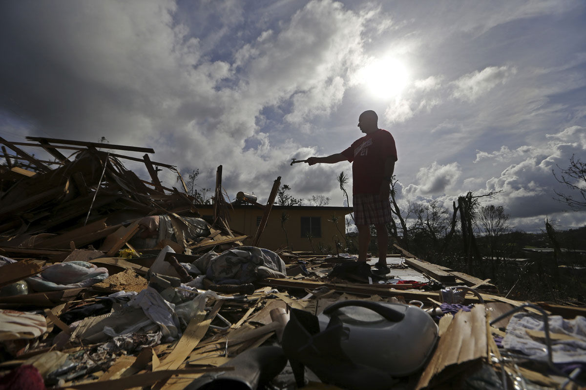Jose Garcia Vicente holds a piece of plumbing he picked up, as he shows his destroyed home, in the aftermath of Hurricane Maria, in Aibonito, Puerto Rico, Monday, Sept. 25, 2017. The U.S. ramped up its response Monday to the humanitarian crisis in Puerto Rico while the Trump administration sought to blunt criticism that its response to Hurricane Maria has fallen short of it efforts in Texas and Florida after the recent hurricanes there. (AP Photo/Gerald Herbert)