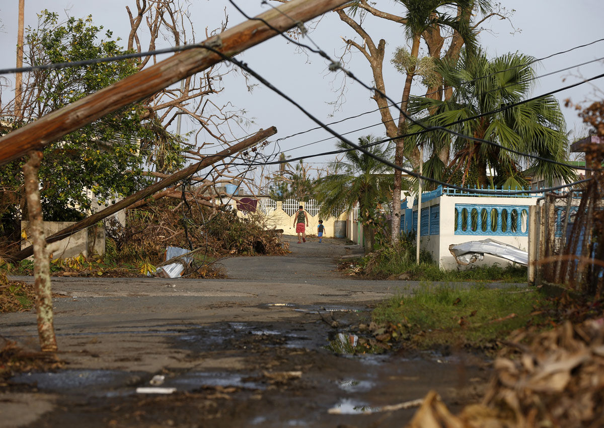 A man and child walk down street strewn with debris and downed power lines in the aftermath of Hurricane Maria, in Yabucoa, Puerto Rico, Tuesday, Sept. 26, 2017. Governor Ricardo Rossello and Resident Commissioner Jennifer Gonzalez, the island's representative in Congress, have said they intend to seek more than a billion in federal assistance and they have praised the response to the disaster by President Donald Trump, who plans to visit Puerto Rico next week, as well as FEMA Administrator Brock Long.  (AP Photo/Gerald Herbert)