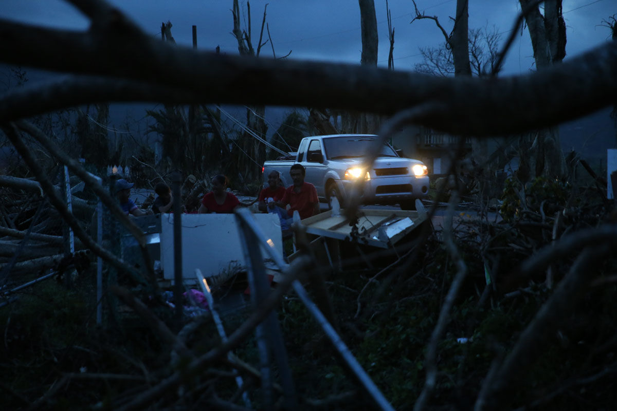 Evan Mandino, right, sits with neighbors on a couch outside their destroyed homes as sun sets in the aftermath of Hurricane Maria, in Yabucoa, Puerto Rico, Tuesday, Sept. 26, 2017. (AP Photo/Gerald Herbert)