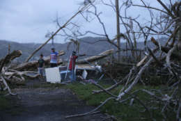 Evan Mandino stands among debris outside his destroyed home as sun sets in the aftermath of Hurricane Maria, in Yabucoa, Puerto Rico, Tuesday, Sept. 26, 2017. (AP Photo/Gerald Herbert)