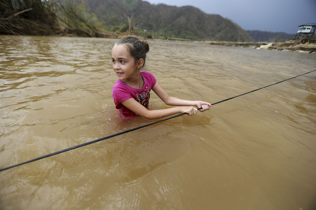 Ruby Rodriguez, 8, looks back at her mother as she crosses the Rio San Lorenzo Morovis with her family, since the bridge was swept away by Hurricane Maria, in Morovis, Puerto Rico, Wednesday, Sept. 27, 2017. They were returning to their home after visiting family on the other side. (AP Photo/Gerald Herbert)