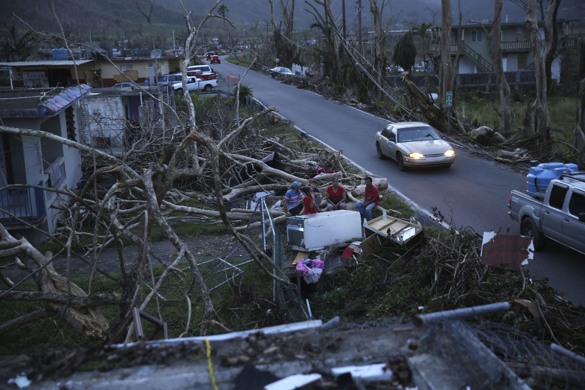 Neighbors sit on a couch outside their destroyed homes as sun sets in the aftermath of Hurricane Maria, in Yabucoa, Puerto Rico, Tuesday, Sept. 26, 2017. (AP Photo/Gerald Herbert)