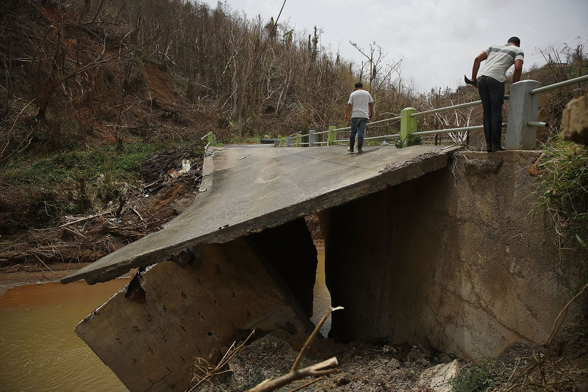 COROZAL, PUERTO RICO - SEPTEMBER 27:  People cross a bridge what was destroyed when Hurricane Maria passed through on September 27, 2017 in Corozal, Puerto Rico.  Puerto Rico experienced widespread, severe damage including most of the electrical, gas and water grids as well as agricultural destruction after Hurricane Maria, a category 4 hurricane, passed through.  (Photo by Joe Raedle/Getty Images)
